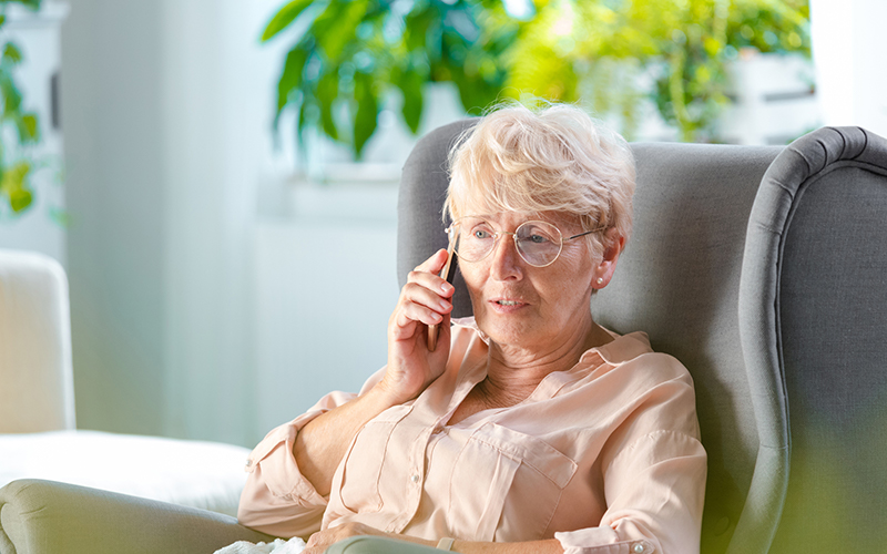 Older woman sitting in a chair setting up her emergency line with peoples rural telephone